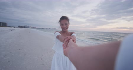 takip etmek : POV romantic Young couple holding hands woman leading boyfriend at beach sunset. Travel holidays vacation concept.
