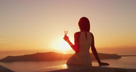 visszavonulás : Luxury lifestyle - Woman drinking champagne at sunset. Elegant lady holding wine class looking at sunset over the ocean enjoying amazing view on luxury travel vacation. SLOW MOTION shot on RED EPIC. Stock mozgókép