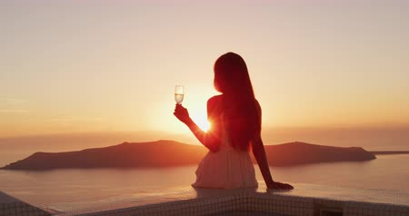bílé víno : Woman at sunset. Luxury lifestyle - Woman drinking champagne. Elegant lady holding wine class looking at sunset over the ocean enjoying amazing view on luxury travel vacation. SLOW MOTION shot on RED.