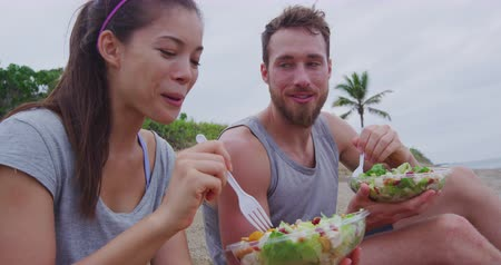 sağlıklı beslenme : Salad - healthy fitness woman and man couple talking and eating food lunch sitting on beach after workout. Mixed race Asian Caucasian female model and male models in sportswear.