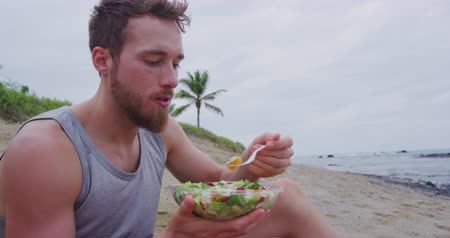 preparado : Fitness man eating healthy salad meal at workout. Handsome young muscular male adult sitting on the beach after running workout for lunch break with fresh prepared to go vegan raw vegetables food. Stock Footage