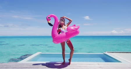 pelicans : Vacation woman in bikini with inflatable pink pelican pool toy mattress by swimming pool. Elegant lady relaxing sunbathing enjoying travel holidays at resort pool. Luxury lifestyle travel concept,