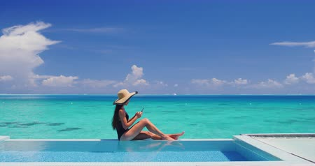 sunhat : Woman using mobile cell phone app on vacation sitting af pool by tropical ocean coral lagoon on travel holidays. Slow motion. Stock Footage