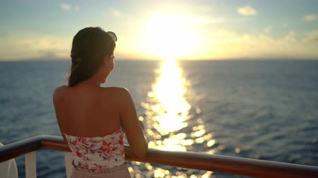 лайнер : Cruise ship vacation travel woman enjoying sunset at sea on boat with beautiful sunset on travel at on the ocean. Relaxed elegant young woman enjoying luxury travel. Asian Chinese  Caucasian woman. Стоковые видеозаписи