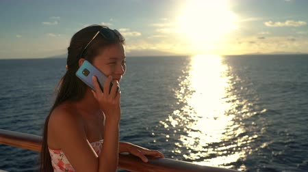 hírnök : Woman talking on phone - Woman using mobile phone on Cruise ship vacation travel lady enjoying sunset at sea on boat with beautiful sunset on travel.
