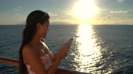 sosyal ağ : People using phones - Woman using mobile smart phone on Cruise ship vacation travel woman enjoying sunset at sea on boat with beautiful sunset on travel at sea.
