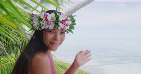 çelenk : Tahiti beauty woman wearing flower head wreath traditional Tahitian cultural accessory flower crown. Bora Bora, French Polynesia. Beautiful Asian multiracial girl waving hand saying hello hi welcome. Stok Video
