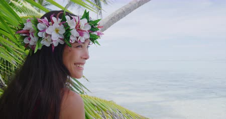 orchidea : Exotic beauty wellness woman relaxing on tropical beach with Tahiti flower wreath crown hair accessory. Bora Bora, French Polynesia. Travel vacation girl smiling happy. Stock mozgókép