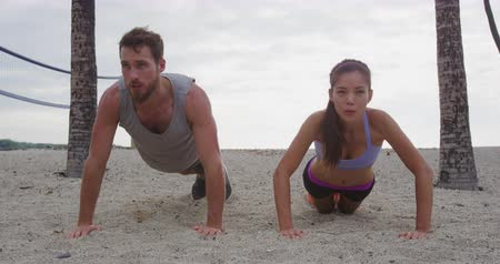 Çapraz kollar : Pushups fitness woman and man exercising push-ups on beach outdoors. Fit male and female fitness trainers working out training in summer on beach in warm sunny sunset. RED EPIC SLOW MOTION.