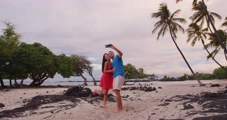 elvonult : Selfie couple on Hawaii beach vacation with palm trees in Big island of Hawaii, USA. Hawaiian holidays getaway. Happy people on summer holidays Stock mozgókép