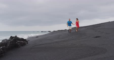 elvonult : Couple walking during travel holidays on secluded black sand beach. Full length shot of people in love running together having fun during summer travel vacation on Big Island, Hawaii, USA. Stock mozgókép