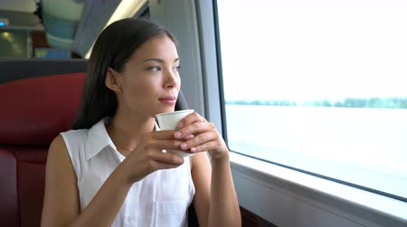 train workers : Asian woman traveling in train drinking morning coffee on commute to work. Businesswoman on travel commuting to work in business class.