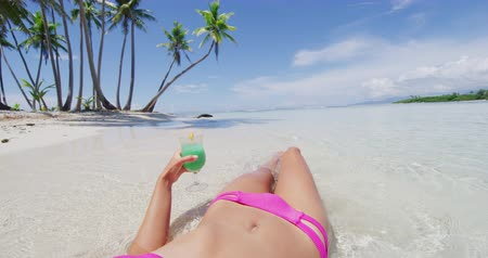 Канкун : Beach vacation woman sun tanning drinking blue Hawaiian drink on suntan summer relax background. Girl hand holding cocktail glass sunbathing body and legs.
