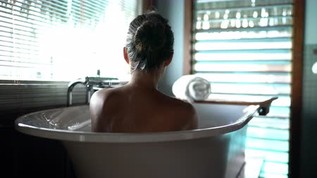 hotel suite : Luxury bath woman relaxing in hot bathtub in hotel resort suite room enjoying pampering spa moment lifestyle. Stock Footage