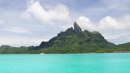 mt : Bora Bora and Mount Otemanu in Tahiti, French Polynesia with yacht, coral lagoon sea and Mt Pahia, Mt Otemanu, Tahiti, south Pacific Ocean. 59.94 FPS slow motion. Stock Footage