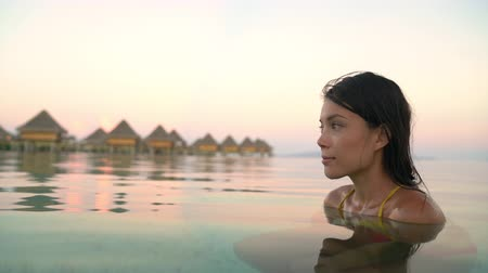 bora bora : Travel luxury hotel serene calm beauty woman relaxing on beach summer vacation in water at sunset. Stock Footage
