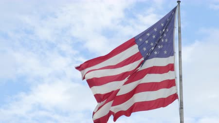 glória : American Flag - US flag waving in wind. USA flag on clear blue sky. Official flag of the United States of America, AKA The Stars and Stripes, Red, White, and Blue, Old Glory, The Star-Spangled Banner.