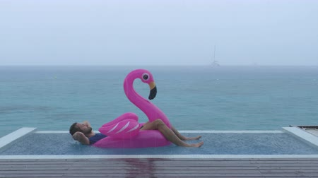 doughnut : Vacation rain - funny video of holidays getaway travel raining away under heavy rainfall with relaxing and happy man smiling on flamingo float in luxury pool with funny face expression.
