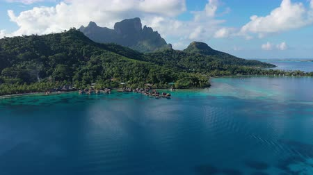 タヒチ島 : Travel vacation aerial drone video of Bora Bora paradise and overwater bungalows luxury resort hotel, coral reef lagoon ocean beach. Mount Otemanu, French Polynesia, Tahiti, South Pacific Ocean 動画素材