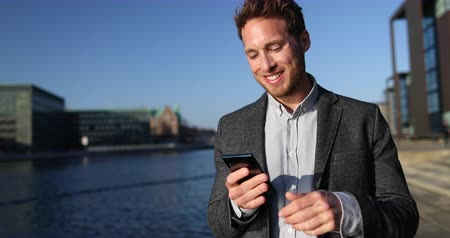 kopenhagen : Business man Using Smartphone App in City Business District. Business Man on Mobile Phone in SLOW MOTION 59.94 FPS, 4K (UHD). From Copenhagen, Denmark, Scandinavia. Stockvideo