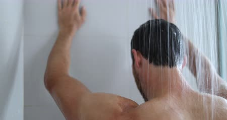 saç kremi : Man in shower showering in bathroom at home. Unrecognizable person from behind warm bath in modern bathroom. hands against wall maybe tired and depressed or maybe relaxing serene.