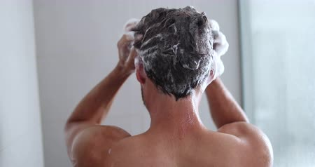 cleaning products : Man taking a shower washing hair with shampoo product under water falling from luxury rain shower head. Morning routine luxury hotel lifestyle guy showering. body care hygiene.