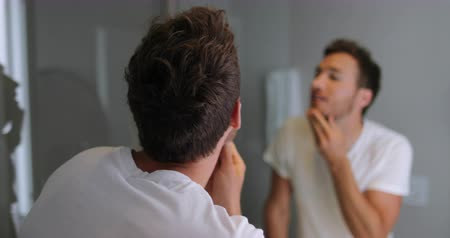 beard trim : Man face care looking in mirror touching his beard or skin health. Male beauty morning skincare routine in home bathroom. After shave men lifestyle concept. Applying natural oil or similar