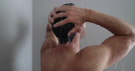 cleaning products : Man in shower washing hair showering in bathroom at home. Unrecognizable person from behind rinsing shampoo and conditioner from hair in warm bath with modern bathroom. Stock Footage