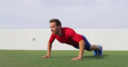 sportowiec : Fit man doing push ups exercise at outdoor gym. Full body workout athlete doing pushup on grass working out exercising core and arms. Real time 29.97 FPS. See other exercises.