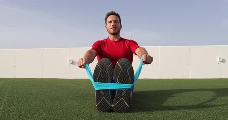 pull out : Fitness man training shoulders back and arms with resistance bands at outdoor gym. Body workout with equipment outside. Elastic rubber band accessory.