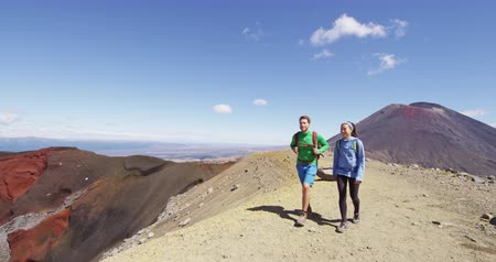 great video : Adventure people hiking on nature trek in mountains on sunny day. Man and woman couple backpackers walking towards summit in Tongariro National Park, New Zealand. People living healthy lifestyle.