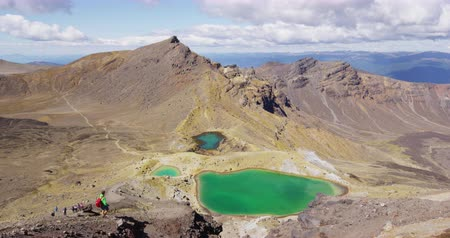 tramp : Hiking man tramping with view from Summit of Emerald Lakes New Zealand. Backpacker hiking Tongariro Alpine Crossing. Spectacular landscape, Tongariro National Park, New Zealand Stock Footage