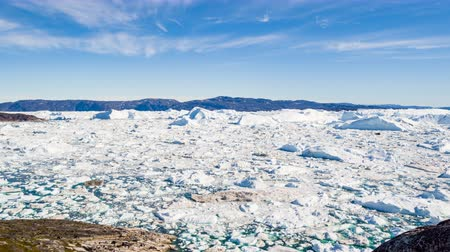 disko : Travel in arctic landscape nature with icebergs. Greenland tourist man explorer looking at amazing view of Greenland icefjord affected by climate change and global warming. Iceberg in Ilulissat.