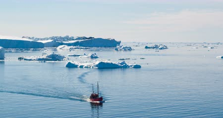disko bay : Icebergs and fishing and tourist boat in Greenland iceberg landscape of Ilulissat icefjord with giant icebergs. Icebergs from melting glacier. Aerial drone video footage of arctic nature. Ecotourism.