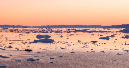 disko bay : Icebergs and fishing and tourist boat in Greenland iceberg landscape of Ilulissat icefjord with giant icebergs. Icebergs from melting glacier. Aerial drone video footage of arctic nature at sunset.