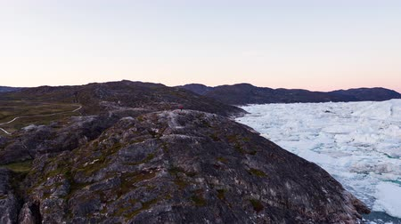 disko : Travel in arctic landscape nature with icebergs - Greenland tourist man explorer - tourist person looking at amazing view of Greenland icefjord - aerial video. Man by ice and iceberg in Ilulissat.