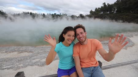 salva : New Zealand travel. Tourists couple at Champagne pool at Wai-O-Tapu pools Sacred Waters waving hello saying hi to camera. Tourist attraction in Waiotapu, Rotorua, Okataina Volcanic Centre, Taupo.