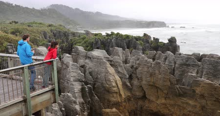 к юго западу : New Zealand Punakaiki Pancake Rocks tourists couple travel taking photos in Paparoa National Park, West Coast, South Island, New Zealand. 59.94 FPS slow motion.