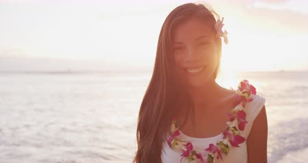 orchideák : Woman portrait video looking at camera smiling. Hawaii woman wearing lei flower necklace on beach sunset for luau party or honeymoon wedding in Waikiki beach, Honolulu, holiday travel. SLOW MOTION