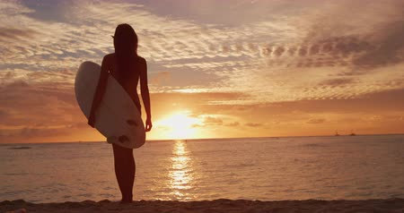strandlaken : Young beautiful surfer woman standing with surfboard on the beach with the sea and surf in the background in dawn light, Shot in 4K on RED camera in SLOW MOTION.