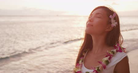 гавайский : Mindfulness - mindful meditating woman serene breathing calm and relaxed with eyes closed on beach doing meditation wearing traditional Hawaii lei on Hawaiian sunset beach. Multiracial model. Slowmo. Стоковые видеозаписи