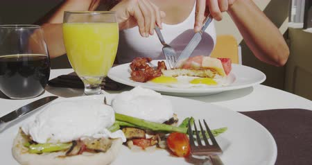 poached egg : Breakfast Eggs Benedict and bacon and eggs, hash browns and orange juice at restaurant outside. Couple eating breakfast closeup in SLOW MOTION.