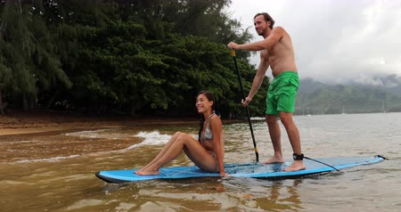 sucção : Stand up paddleboard - couple on paddle board doing ocean watersport activity at Puu Poa beach, Hanalei Bay, Kauai, Hawaii, USA. Hawaii travel fun swimwear woman and man romantic adventure. Stock Footage