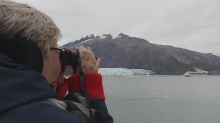 glacier national park : Senior tourist looking at Alaska Glacier Bay landscape using binoculars on cruise ship. Active vacation travel looking at Margerie Glacier and wildlife and enjoying cruising famous tourist destination Stock Footage