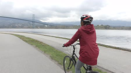 ingiliz columbia : Cyclist biking in Stanley Park by Lions Gate Bridge on Vancouver Seawall. Bike rental is a popular tourist activity in Vancouver, British Columbia, Canada.