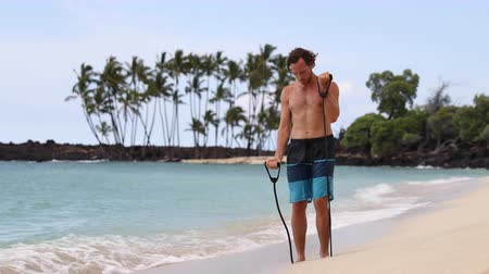 biceps curls : Fitness man exercising biceps with elastic resistance band - Bicep Curl arm exercise on beach. Fit male sport fitness model showing workout exercise. REAL TIME.