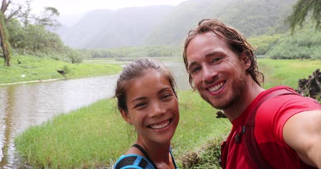 havaiano : Couple taking selfie video smiling happy having fun in the rain on travel on Hawaii. Big Island black sand beach beach and hike in Pololu Valley - couple hike Vídeos
