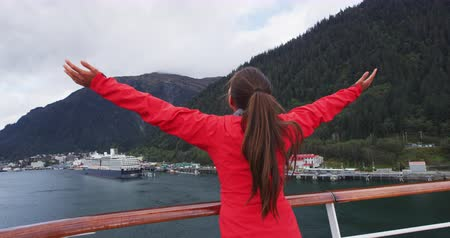 аляскинским : Cruise ship passenger in Alaska city of Ketchikan standing on cruise ship deck while sailing Inside Passage. Tourist lifting raising arms serene, happy and cheerful enjoying cruise travel. SLOW MOTION Стоковые видеозаписи