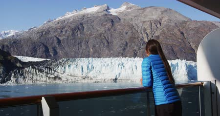 аляскинским : Alaska cruise ship tourist looking at glacier front in Glacier Bay National Park, USA. Woman on travel vacation sailing enjoying view of Margerie Glacier. RED Cinema Camera SLOW MOTION.