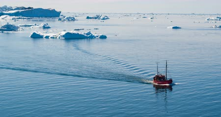 disko bay : Greenland Icebergs and fishing and tourist boat in Greenland iceberg landscape of Ilulissat icefjord with giant icebergs. Aerial drone video footage of arctic nature. Ecotourism. Stock Footage